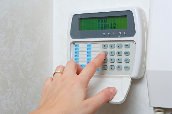 Person pressing buttons on alarm system keypad