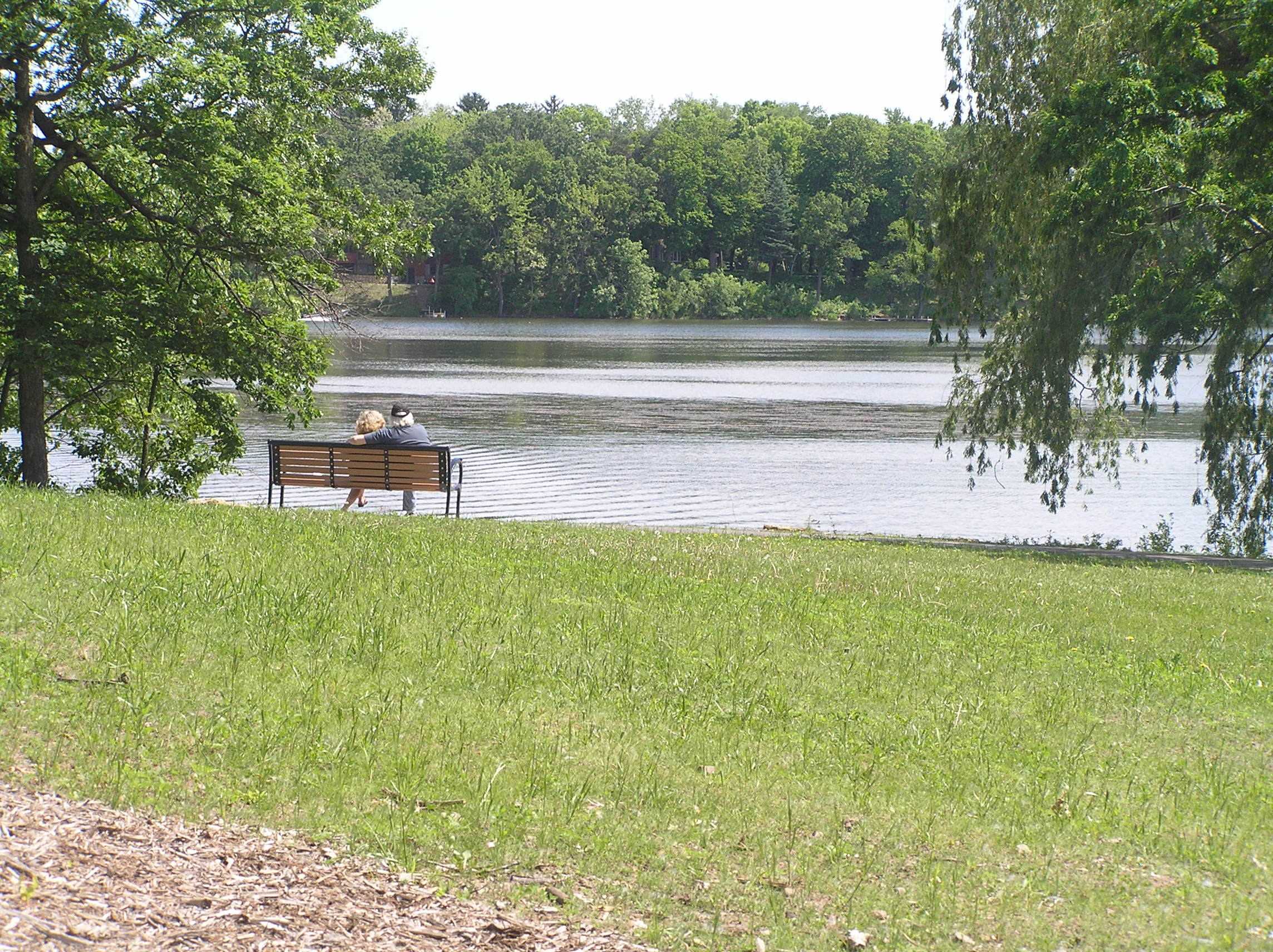Two People Sitting on a Bench by a Lake