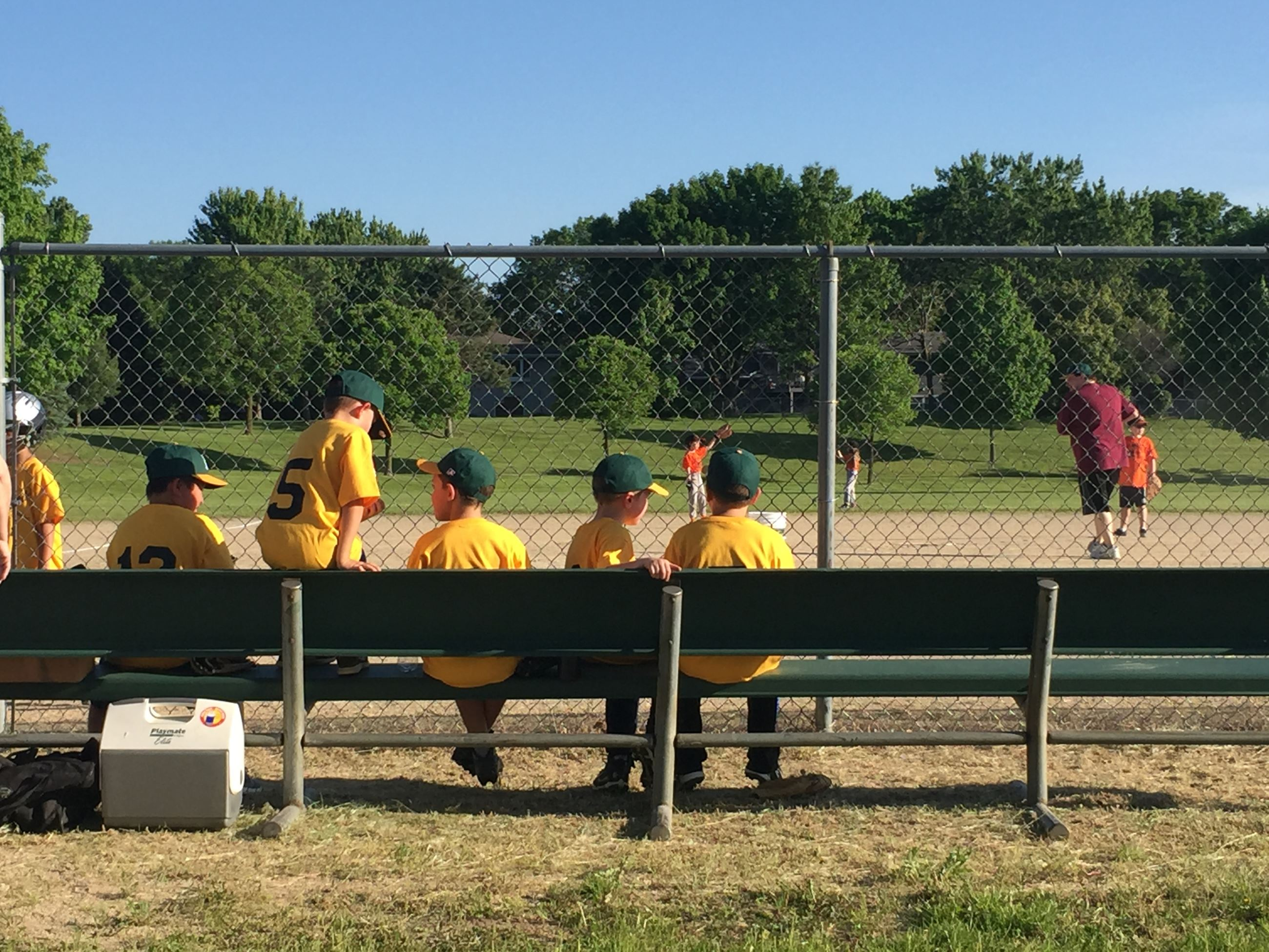 Kids Sitting on a Bench at a Baseball Game