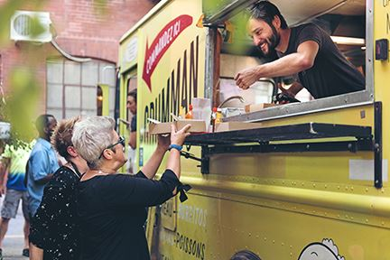 Man serving customers from a food truck window