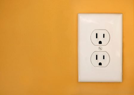 Electrical outlet on orange wall
