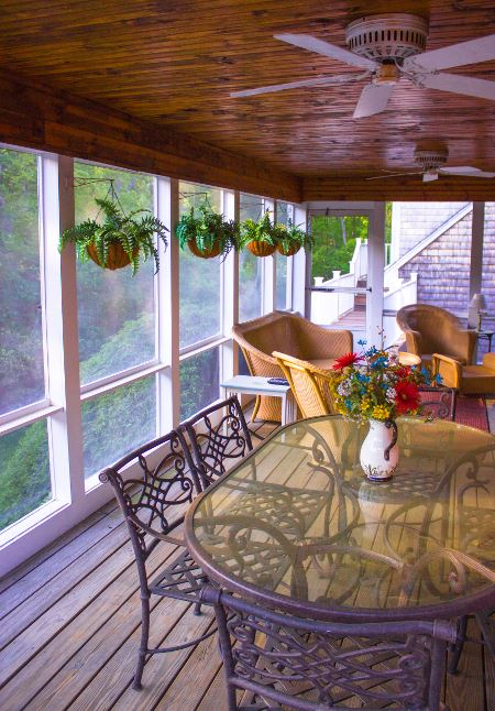 Enclosed porch with dining table, hanging plants, and furniture