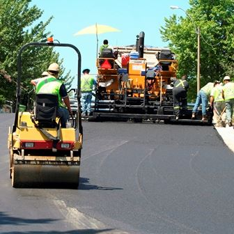 Workers using machines to pave a street